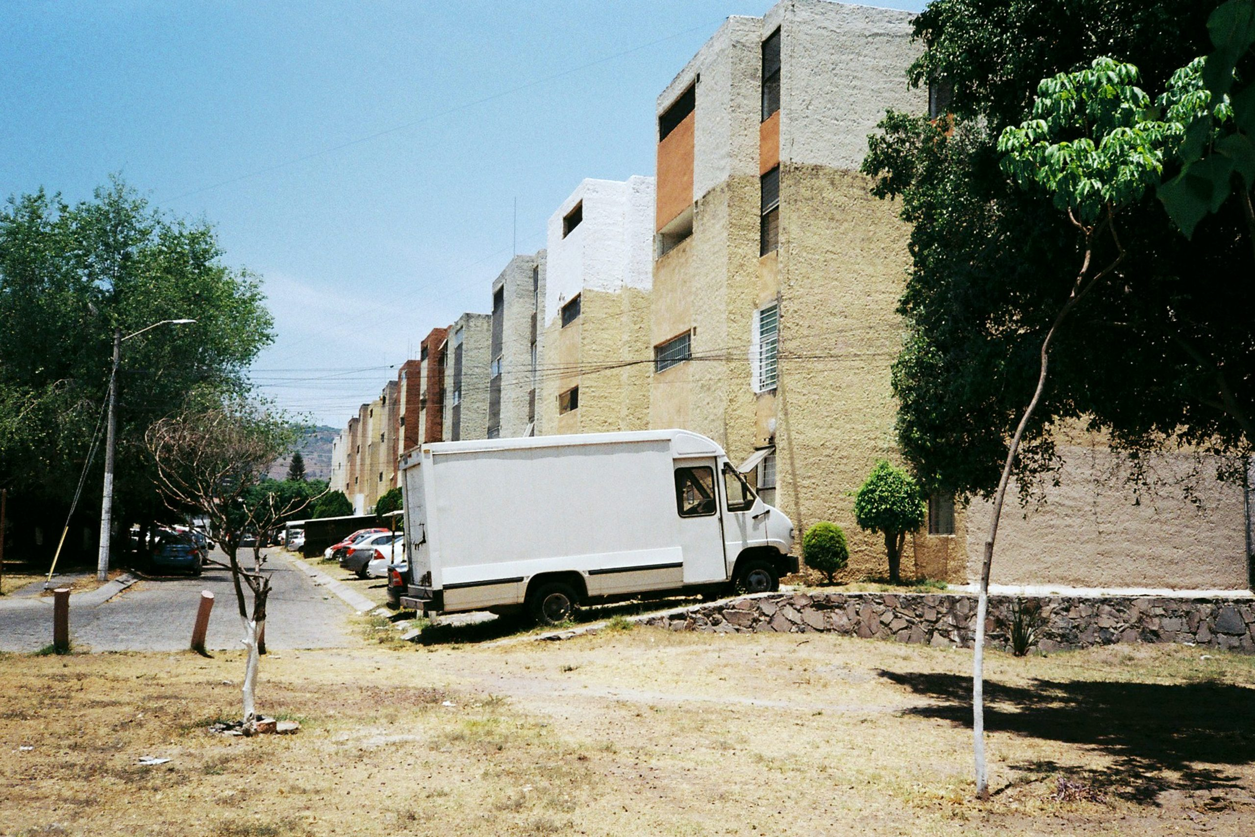 white van parked beside brown concrete building during daytime